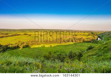 View of flat plain and river valley from a high hill.