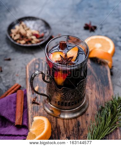 Mulled wine with orange and spices in vintage glass cup holder on wooden board. Concrete background. Hot drink. Top view.