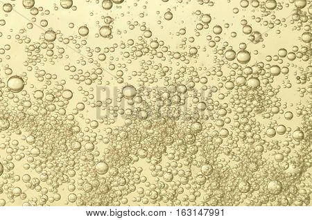 Champagne fizz bubbles soars over a golden background