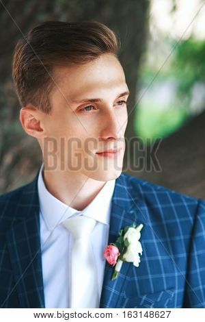 Gorgeous smiling groom. Handsome groom at wedding tuxedo smiling and waiting for bride.Elegant man in blue costume and white tie.