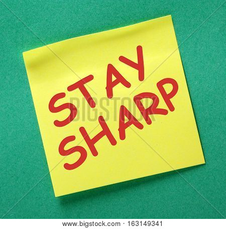 The words Stay Sharp in red text on a yellow sticky note as a reminder to maintain focus in your work and life