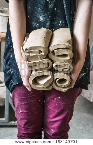 Master potter girl holding a many cut and twisted layers roll of clay pieces. Creative studio potter. Workplace wizard Crock pottery