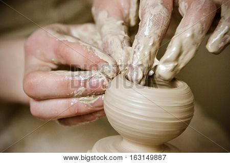 A man with his hands dub wall jug which he sculpts out of clay on a circle. Create clay vessel. Modeling white-clay shaping vessel. Caucasian man making vessel Cclay in circle.