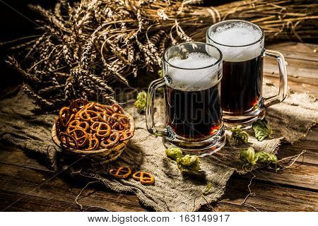 Two tankards beer with wheat and hops , basket of pretzels on wooden table