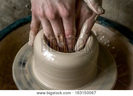 Girl sculpts in clay pot closeup. Modeling clay close-up. Caucasian man making vessel daytime of white clay in fast moving circle. Art creativity. Ukraine cultural traditions. Hobbies
