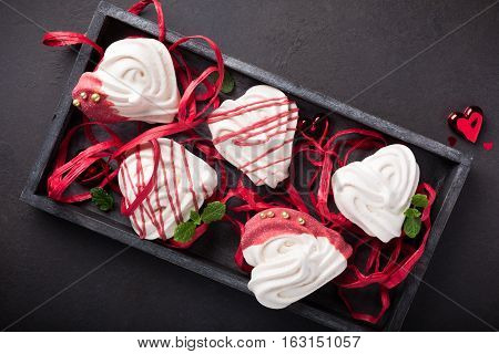 Homemade meringues in heart shape in old wooden box for Valentine's day, top view, copy space.