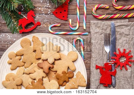 Adorned Christmas table with Christmas cookies, fir branches, cutlery