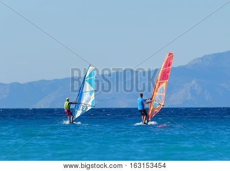 Back view of two windsurfers in the action mooving parallel to each other