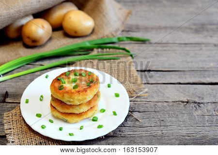 Roasted vegetable patties on a plate. Healthy patties cooked of potatoes, green peas, carrots and green beans. Vegetarian lunch or dinner idea. Fresh vegetables on wooden background with copy space