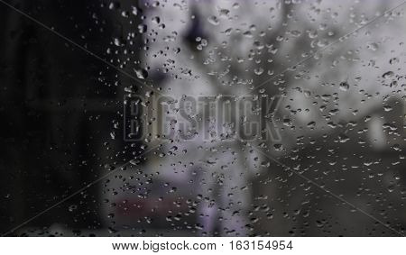 Raining drops on the glass off window for background