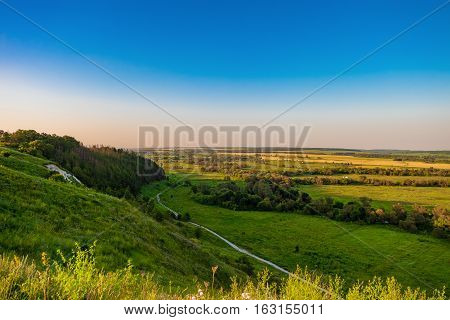 Steep of the chalk mountain overlooking the green plain