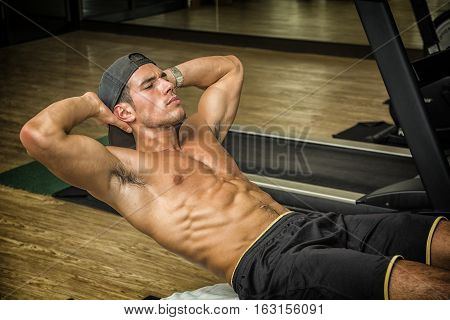 Attractive muscular young man shirtless in gym working out, doing exercises for abs