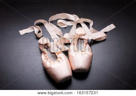 Pair of Ballet Shoes on Wood Background