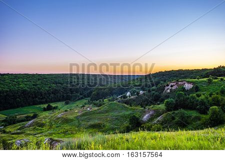 Evening forest on chalk mountains. Camping tourists. Summer landscape.