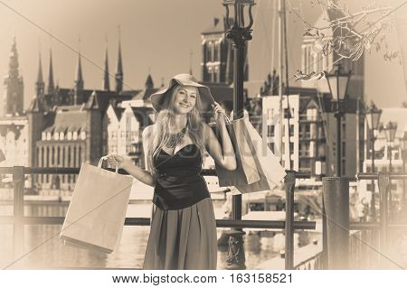 Spending money on sales buying things concept. Fashionable woman relaxing and standing with shopping bags in town wearing glamorous outfit and big sun hat sepia