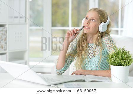 girl using laptop for homework, in her own room
