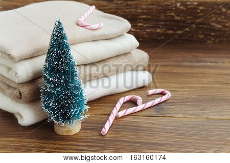 Stack of knitted clothes in beige tones. Cashmere sweaters wool cardigans little Christmas tree and candy cane on a wooden background. Concept of Winter time and Christmas holiday. Copy space.