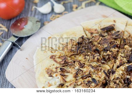 Vegan fried onion like cracklings pie on a wooden table