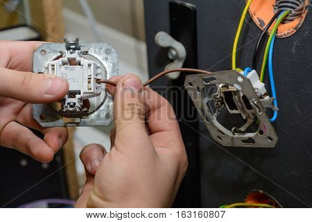 Craftsman installing and installing a switchboard - close-up installation wall