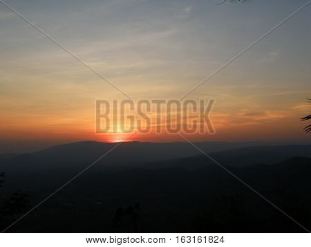 Orange and blue sunset afterglow over the silhouette of mountain range, Thailand