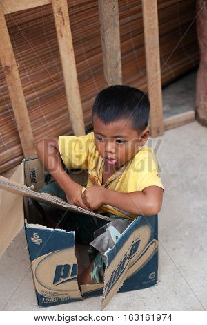 SUMATRA INDONESIA - AUGUST 16,2012: a little boy sitting in a box in the village of Bukit Lawang