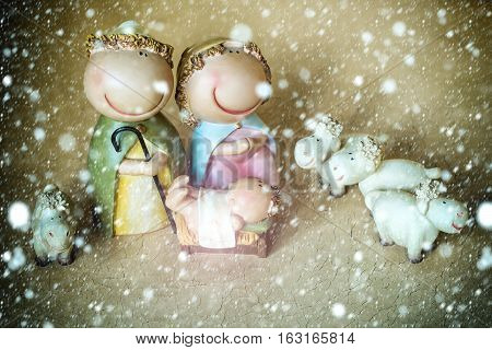 decorative celbrating Christmas and Jesus birth figurines of holy vergin Mary Josepd newborn child with few white sheeps standing on light leather background under snow and snowflakes