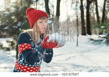 Girl blows snow with mittens and makes a wish. Winter Sunny day