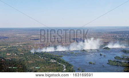 The Zambezi River in Zambia, the break-off edge and the spray of Victoria Falls, in the background a canyon landscape