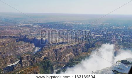 The crashing edge and the spray of the Victoria Falls from the air, the runoff of the Zambezi after the waterfall in a canyon, scenery in Zambia and Zimbabwe