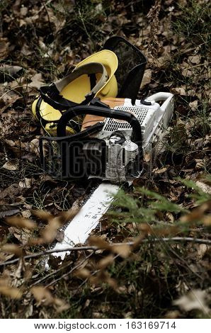 Chainsaw and protective helmet on the forest ground