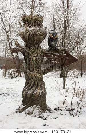 unusual pointer arrow old tree with a crow that holds in its beak a cheese,winter landscape