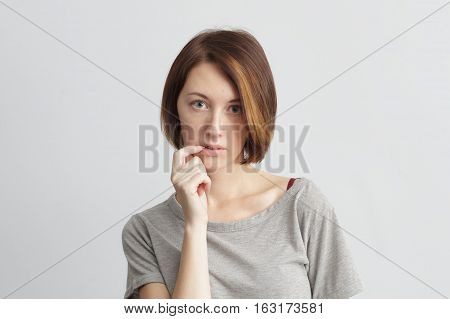 Doubts emotion on pretty girl face. Girl doubts in the choice and bites a fingernail