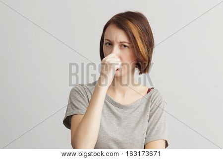 Disgusting smelling. Girl closes her nose because of the odor and stench.