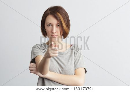 Girl shows index finger forward. Face frowning with displeasure.