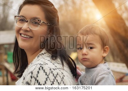 Young Mother With Her Baby Boy In A Baby Carrier Scarf