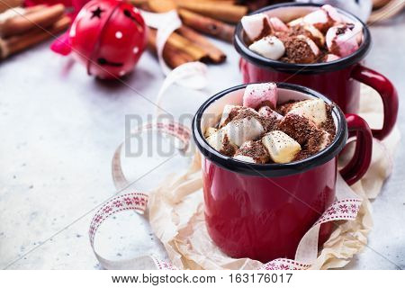 Hot chocolate with marshmallows and spices in red mug on rustic christmas table. Selective focus, tasty holidays concept. Drink for fall and winter, copy space background