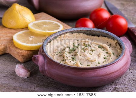 Humus in homemade bowl with lemon and tomatoes on natural wooden desk.