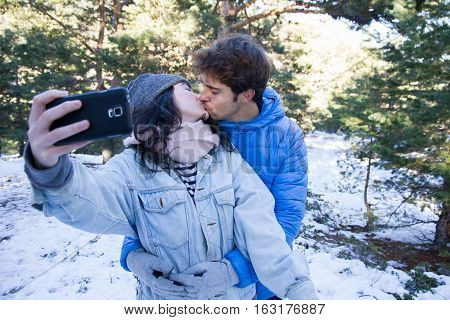 Couple of lovers enjoying in the snow doing a selfie while they are kissing. They are happy, spending a day of vacation in the mountains. - happiness, love, couple, time together concept