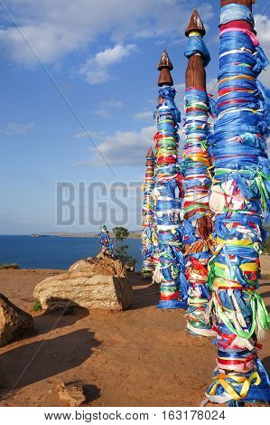 Sacred poles with colored ribbons in island Olkhon. Wooden shaman totems. Burhan Cape Baikal Lake Russian Federation