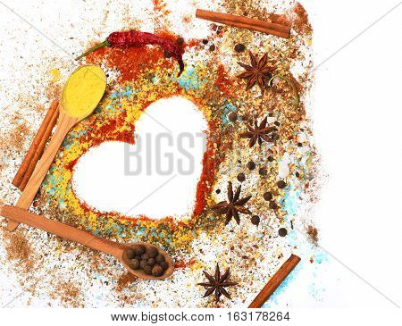 valentine set of ingredients for cooking spicy fragrant spices in spoons with allspice coriander and pepper laurel sheet chili pepper paprika in form of heart isolated on white copy space