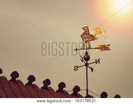 Rooster weather vane on sunset. Golden reflection