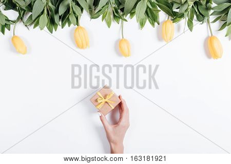 Female Hand Puts A Small Box With A Gift On The Table With Yellow Tulips