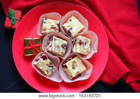 Plate of Christmas fudge made with white chocolate cranberries and pecans with red napkin and miniature gifts
