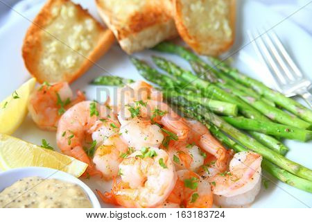 Plate of roasted shrimp and asparagus with garlic bread lemon and mustard sauce