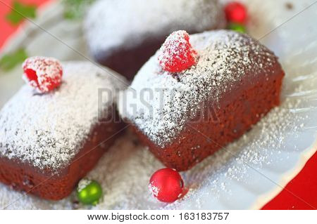 Small chocolate cakes with fresh raspberries and powdered sugar with tiny Christmas ornaments