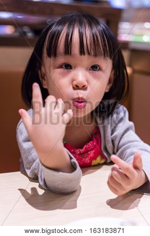 Asian Chinese Little Girl Eating Sushi At A Japanese Restaurant