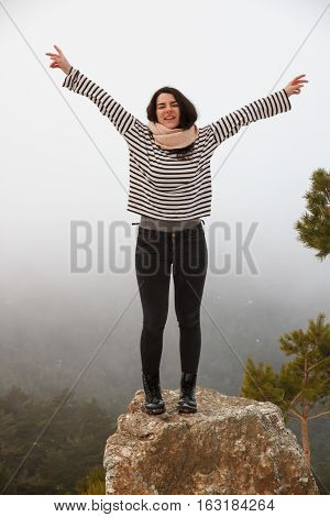 Young caucasian woman screaming for joy on top of a rock in snowy mountain. She is raising her hands because she is enjoying herself - freedom, joy, goals, positivity concept