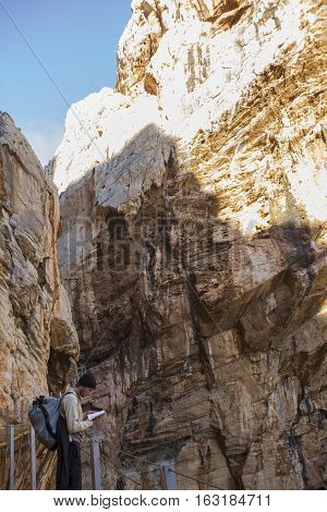 Malaga Spain - December 6 2016: Trekker young man looking up a map at Caminito del Rey path Malaga Spain