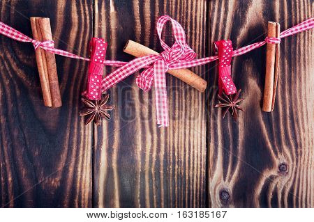 hanging cinnamon and star anises on a rope on a wooden background