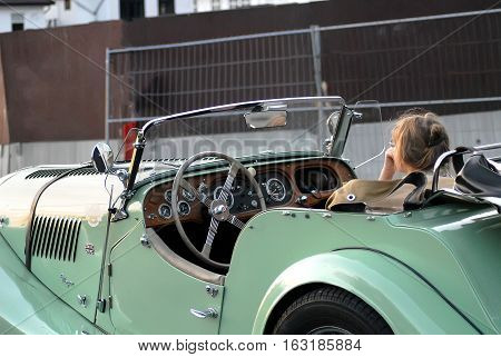 Bergen Norway - July 20 2014: shot of caucasian girl sitting in Morgan Plus 4. Morgan Plus 4 roadster classic car made by the Morgan Motor Company from 1950 to 1969 in parking lot. Classic cars in the center street of Bergen.